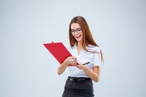 Smiling young business woman in glasses with pen and tablet for notes on a gray background