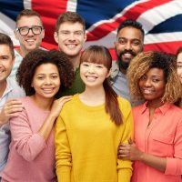 diversity, race, ethnicity and people concept - international group of happy smiling men and women over english flag background