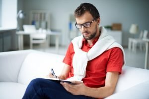 Smart businessman making notes while sitting on sofa in the office