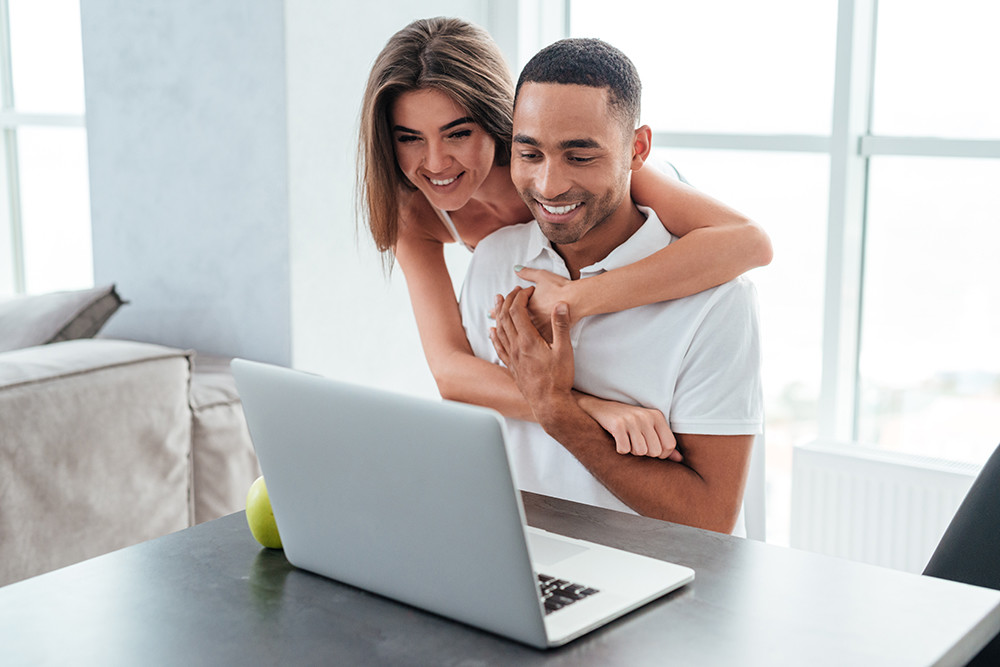 Couple smiling whilst on laptop