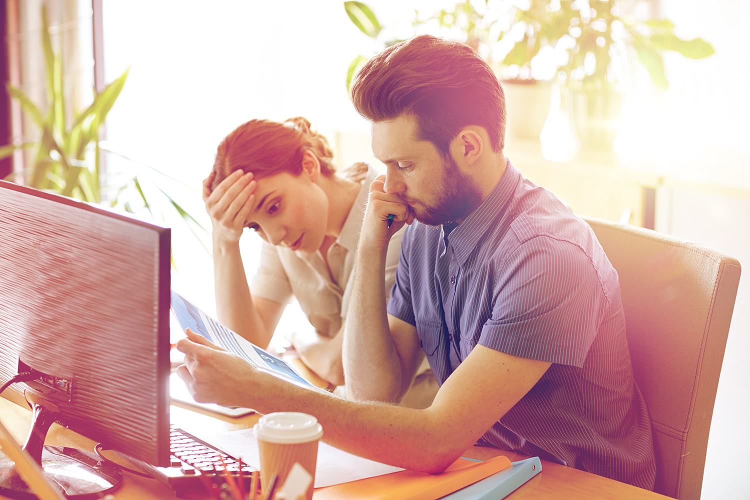 Couple looking stressed whilst reviewing letter at a computer.